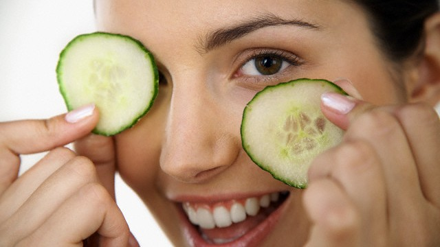 Woman Holding Cucumber Slices over Eyes --- Image by © Mina Chapman/Corbis
